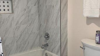 New tile shower, floor, commode, hotel towel rack, shampoo niche.