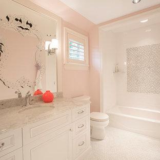 オマハの中サイズのトラディショナルスタイルのおしゃれな子供用バスルーム (アンダーカウンター洗面器、家具調キャビネット、白いキャビネット、珪岩の洗面台、アルコーブ型浴槽、シャワー付き浴槽、分離型トイレ、白いタイル、石タイル、ピンクの壁、磁器タイルの床) の写真