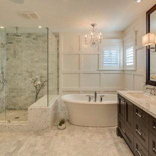 Cette photo montre une salle de bain principale chic de taille moyenne avec un lavabo encastré, un placard avec porte à panneau encastré, des portes de placard en bois sombre, un plan de toilette en granite, une baignoire indépendante, une douche d'angle, un carrelage gris, des carreaux de céramique, un mur blanc et un sol en carrelage de porcelaine.