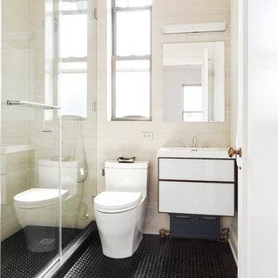 ニューヨークの小さいモダンスタイルのおしゃれなマスターバスルーム (フラットパネル扉のキャビネット、濃色木目調キャビネット、アルコーブ型シャワー、一体型トイレ、ベージュのタイル、磁器タイル、ベージュの壁、大理石の床、壁付け型シンク、珪岩の洗面台、黒い床、開き戸のシャワー) の写真