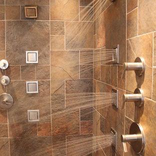 Immagine di una grande stanza da bagno padronale classica con ante con bugna sagomata, ante rosse, WC a due pezzi, piastrelle in gres porcellanato, pavimento in gres porcellanato, lavabo sottopiano, vasca ad angolo, piastrelle marroni, pareti beige e top in granito