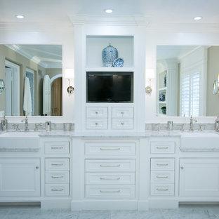 Modelo de cuarto de baño principal, tradicional, grande, con armarios con rebordes decorativos, puertas de armario blancas, encimera de mármol, bañera exenta, baldosas y/o azulejos blancos, paredes beige y suelo de mármol