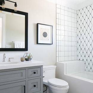 Imagen de cuarto de baño clásico renovado con armarios estilo shaker, puertas de armario grises, paredes beige, sanitario de una pieza y baldosas y/o azulejos blancos