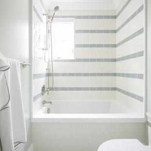 Cette image montre une salle d'eau marine de taille moyenne avec un placard à porte shaker, des portes de placard blanches, une baignoire en alcôve, un combiné douche/baignoire, un WC à poser, un carrelage bleu, un carrelage blanc, des carreaux de béton, un mur vert, un sol en carrelage de porcelaine, un lavabo encastré, un plan de toilette en surface solide, un sol blanc et aucune cabine.