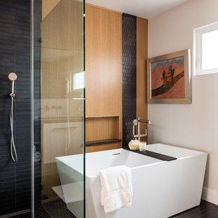 Cette photo montre une salle de bain tendance de taille moyenne avec des portes de placard blanches, une baignoire indépendante, un carrelage noir, un mur beige et un sol noir.