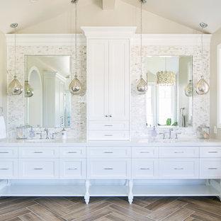 Idee per una stanza da bagno tradizionale con ante con riquadro incassato, ante bianche, piastrelle grigie, piastrelle bianche, piastrelle a mosaico, pavimento marrone e top bianco