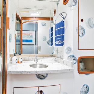 Immagine di una piccola stanza da bagno con doccia costiera con ante lisce, ante bianche, doccia alcova, WC sospeso, pareti multicolore, pavimento in legno massello medio, lavabo sottopiano, top in quarzo composito, pavimento arancione, porta doccia a battente e top multicolore