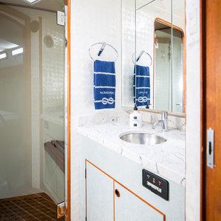 Immagine di una piccola stanza da bagno padronale con ante lisce, ante blu, doccia alcova, WC sospeso, pareti bianche, pavimento in legno massello medio, lavabo sottopiano, top in quarzo composito, pavimento arancione, porta doccia a battente e top multicolore
