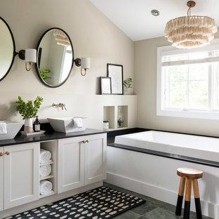 Immagine di una stanza da bagno costiera con ante in stile shaker, ante bianche, vasca da incasso, pareti beige, lavabo a bacinella, pavimento grigio e top nero