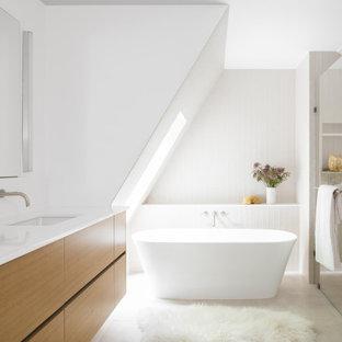 Bild på ett mellanstort funkis vit vitt en-suite badrum, med släta luckor, skåp i ljust trä, ett fristående badkar, en kantlös dusch, en toalettstol med hel cisternkåpa, vit kakel, porslinskakel, vita väggar, klinkergolv i porslin, ett undermonterad handfat, bänkskiva i kvartsit, beiget golv och dusch med gångjärnsdörr