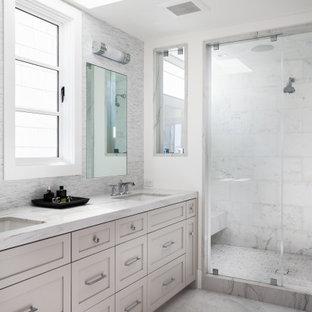 Ejemplo de cuarto de baño principal, marinero, grande, con armarios con paneles empotrados, bañera encastrada sin remate, baldosas y/o azulejos grises, baldosas y/o azulejos de mármol, suelo de mármol, lavabo bajoencimera, encimera de mármol, suelo blanco y encimeras blancas