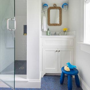 Imagen de cuarto de baño infantil, costero, con armarios con paneles empotrados, puertas de armario blancas, ducha empotrada, baldosas y/o azulejos blancos, baldosas y/o azulejos de cemento, paredes grises y suelo azul