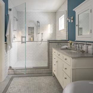 Klassisk inredning av ett mellanstort grå grått en-suite badrum, med luckor med infälld panel, vita skåp, en dusch i en alkov, vit kakel, tunnelbanekakel, blå väggar, ett undermonterad handfat, grått golv, dusch med gångjärnsdörr, ett badkar med tassar, marmorgolv och bänkskiva i kvarts