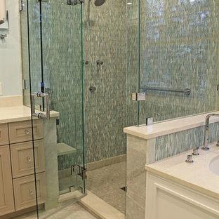 Imagen de cuarto de baño principal, tradicional, de tamaño medio, con armarios con paneles empotrados, puertas de armario beige, bañera encastrada sin remate, ducha empotrada, sanitario de pared, baldosas y/o azulejos verdes, baldosas y/o azulejos de vidrio, paredes azules, suelo de mármol, lavabo bajoencimera, encimera de cuarzo compacto, suelo verde, ducha con puerta con bisagras y encimeras blancas