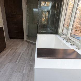 Foto på ett stort funkis en-suite badrum, med släta luckor, bruna skåp, ett fristående badkar, en hörndusch, en toalettstol med separat cisternkåpa, grå kakel, porslinskakel, grå väggar, travertin golv, ett undermonterad handfat, bänkskiva i återvunnet glas, grått golv och dusch med gångjärnsdörr