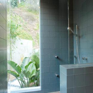 Esempio di una stanza da bagno padronale design di medie dimensioni con lavabo sottopiano, ante lisce, ante in legno chiaro, top in pietra calcarea, vasca ad alcova, vasca/doccia, WC monopezzo, piastrelle blu, piastrelle di vetro, pareti bianche e pavimento in gres porcellanato