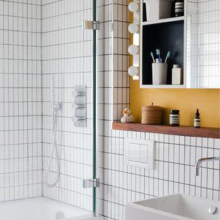 Diseño de cuarto de baño infantil, retro, con lavabo sobreencimera, armarios abiertos, encimera de madera, bañera encastrada, combinación de ducha y bañera y baldosas y/o azulejos blancos
