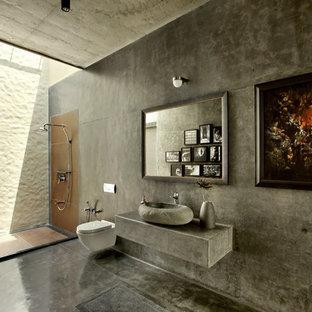Bild på ett tropiskt badrum, med en öppen dusch, en vägghängd toalettstol, betonggolv, ett fristående handfat, grå väggar och med dusch som är öppen