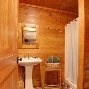 Immagine di una piccola stanza da bagno con doccia rustica con WC a due pezzi, pavimento in mattoni, lavabo a colonna, pavimento rosso e doccia con tenda