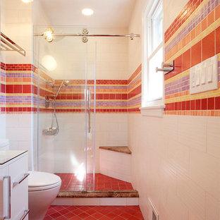 Inredning av ett modernt badrum, med röd kakel, mosaik, släta luckor, vita skåp, en dusch i en alkov och rött golv