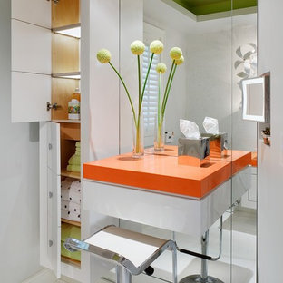 Cette image montre une salle de bain minimaliste avec un placard à porte plane, des portes de placard blanches, un carrelage blanc et un plan de toilette orange.