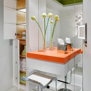 Foto på ett funkis orange badrum, med släta luckor, vita skåp och vit kakel