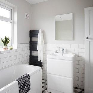 Nordisches Badezimmer mit flächenbündigen Schrankfronten, gelben Schränken, weißen Fliesen, Metrofliesen, grauer Wandfarbe und buntem Boden in Sonstige
