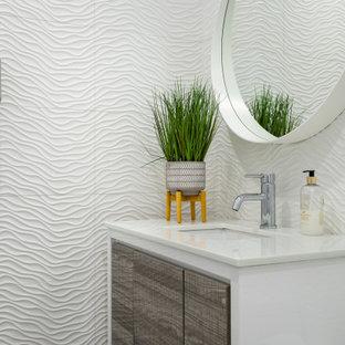 Modern inredning av ett litet vit vitt badrum, med släta luckor, bruna skåp, en toalettstol med separat cisternkåpa, vit kakel, porslinskakel, vita väggar, laminatgolv, ett undermonterad handfat och grått golv