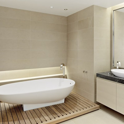 Example of a trendy limestone tile freestanding bathtub design in San Francisco with a vessel sink
