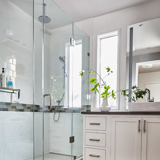 Inspiration for a transitional white tile and subway tile medium tone wood floor and brown floor corner shower remodel in San Francisco with shaker cabinets, white cabinets, white walls, a vessel sink and a hinged shower door
