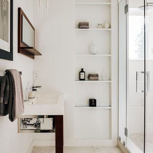 Example of a small trendy bathroom design in San Francisco with open cabinets, white walls, a pedestal sink and a hinged shower door