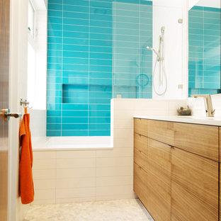 Ejemplo de cuarto de baño infantil, moderno, con armarios con paneles lisos, bañera empotrada, combinación de ducha y bañera, baldosas y/o azulejos azules, suelo de baldosas tipo guijarro y puertas de armario de madera clara