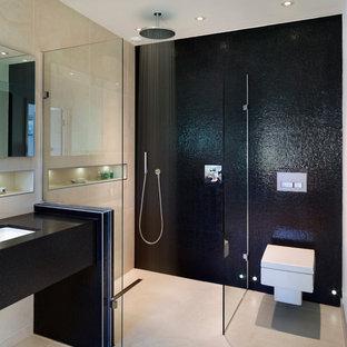 Foto di una stanza da bagno design con lavabo sottopiano, doccia aperta, WC sospeso, piastrelle nere, piastrelle a mosaico e doccia aperta
