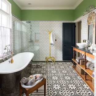 Inspiration for a farmhouse ensuite bathroom in Atlanta with freestanding cabinets, medium wood cabinets, a freestanding bath, a built-in shower, white tiles, metro tiles, grey walls, cement flooring, a vessel sink, multi-coloured floors, an open shower and black worktops.