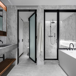 Bathroom - large contemporary master marble tile and gray tile concrete floor and gray floor bathroom idea in New York with an integrated sink, concrete countertops, a hinged shower door, gray countertops, open cabinets and gray walls