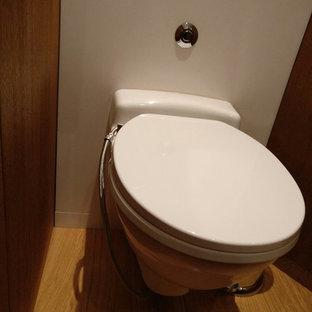 Immagine di una piccola stanza da bagno padronale design con WC sospeso, piastrelle bianche, lastra di pietra, pareti bianche, pavimento in bambù e pavimento marrone