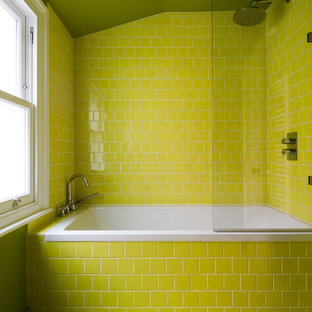 Inspiration for a small contemporary family bathroom in London with flat-panel cabinets, green cabinets, a built-in bath, a built-in shower, a wall mounted toilet, green tiles, ceramic tiles, green walls and a wall-mounted sink.