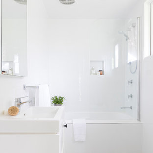 Photo of a contemporary 3/4 bathroom in Brisbane with flat-panel cabinets, white cabinets, an alcove tub, a shower/bathtub combo, white walls, a vessel sink, beige floor, a hinged shower door and white benchtops.