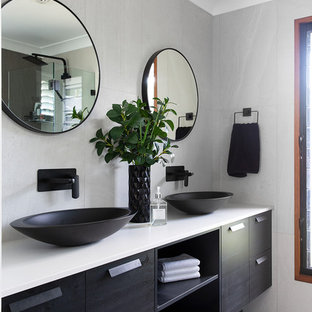 Inspiration for a beach style bathroom in Sunshine Coast with flat-panel cabinets, black cabinets, gray tile, grey walls, a vessel sink, grey floor and white benchtops.