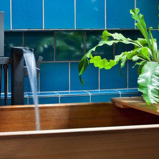Modelo de cuarto de baño principal, minimalista, pequeño, sin sin inodoro, con armarios con paneles lisos, puertas de armario de madera oscura, bañera japonesa, baldosas y/o azulejos azules, baldosas y/o azulejos de cerámica, paredes azules, suelo de baldosas de cerámica, lavabo integrado, encimera de cuarcita, suelo azul y ducha con puerta con bisagras
