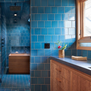 Свежая идея для дизайна: маленькая главная ванная комната в стиле модернизм с плоскими фасадами, фасадами цвета дерева среднего тона, японской ванной, душевой комнатой, синей плиткой, керамической плиткой, синими стенами, полом из керамической плитки, монолитной раковиной, столешницей из кварцита, синим полом и душем с распашными дверями - отличное фото интерьера