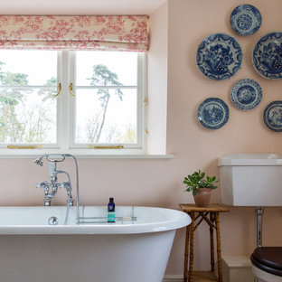 Traditional ensuite bathroom in London with a claw-foot bath, a two-piece toilet, pink walls and beige floors.