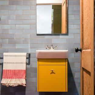 Ispirazione per una stanza da bagno contemporanea con ante lisce, ante gialle, piastrelle blu, piastrelle in ceramica, pareti blu, pavimento con piastrelle in ceramica e lavabo sospeso