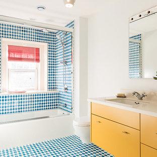 Modernes Badezimmer mit flächenbündigen Schrankfronten, gelben Schränken, Badewanne in Nische, Duschbadewanne, Wandtoilette, blauen Fliesen, farbigen Fliesen, weißen Fliesen, weißer Wandfarbe, Unterbauwaschbecken und Schiebetür-Duschabtrennung in Boston