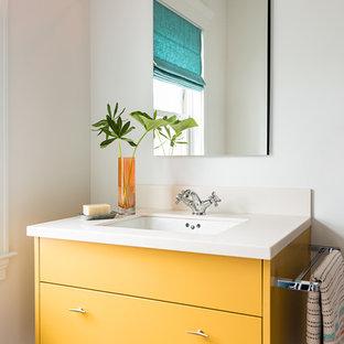 Idéer för ett modernt badrum, med gula skåp, vita väggar, ett undermonterad handfat och släta luckor