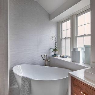 Ejemplo de cuarto de baño principal, ecléctico, de tamaño medio, con armarios con paneles lisos, puertas de armario de madera oscura, bañera exenta, ducha esquinera, sanitario de una pieza, baldosas y/o azulejos blancos, baldosas y/o azulejos de porcelana, paredes blancas, suelo de baldosas de porcelana, lavabo sobreencimera, encimera de cuarzo compacto, suelo gris, ducha con puerta con bisagras y encimeras blancas