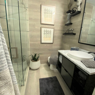 Example of a mid-sized minimalist 3/4 gray tile and ceramic tile light wood floor and beige floor bathroom design in Austin with a vessel sink, flat-panel cabinets, black cabinets, granite countertops and gray countertops
