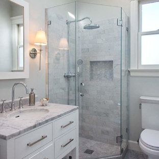 Corner shower - small transitional 3/4 stone tile marble floor corner shower idea in San Francisco with furniture-like cabinets, white cabinets, a one-piece toilet, an undermount sink, marble countertops and white walls
