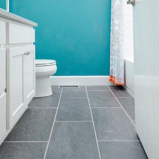 Diseño de cuarto de baño con ducha, ecléctico, pequeño, con armarios estilo shaker, puertas de armario blancas, bañera empotrada, combinación de ducha y bañera, sanitario de una pieza, paredes azules, suelo de baldosas de cerámica, encimera de granito, suelo gris y ducha con cortina