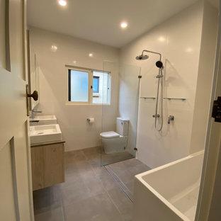Идея дизайна: маленькая главная ванная комната в современном стиле с фасадами островного типа, серыми фасадами, угловой ванной, душевой комнатой, унитазом-моноблоком, белой плиткой, керамогранитной плиткой, белыми стенами, полом из керамогранита, настольной раковиной, столешницей из искусственного кварца, серым полом, открытым душем, серой столешницей, нишей, тумбой под две раковины, подвесной тумбой, многоуровневым потолком и кирпичными стенами